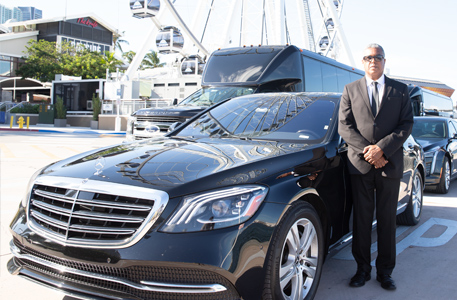 Driver posing beside a black Luxury Sedan