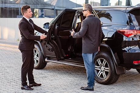 Driver opening luxury car door for passenger to enter