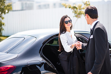 Chauffeur Helping Passenger to Get Out of Luxury Car