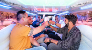 Bachelor party with group of friends having fun inside a stretch limousine by Mundi Limos